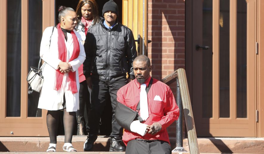 Family members follow Shawn DeLoatch, foreground right, as he steps out of St. Ann's Church in Nyack, N.Y., for a moment before his wife's funeral Thursday, Feb. 28, 2019. Melissa DeLoatch, a pregnant mother of six, was killed when her family was run over outside a Haverstraw, N.Y. convenience store on Feb. 20, 2019. Police allege that a driver intentionally plowed into the family after words were exchanged about his smoking. (Tania Savayan/The Journal News via AP)