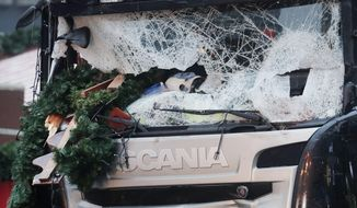 FILE - In this Dec. 20, 2016 file photo Christmas decoration sticks in the smashed window of the cabin of a truck which ran into a crowded Christmas market Monday evening killing several people in Berlin, Germany. (AP Photo/Markus Schreiber, file)