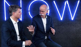 File -- In this Friday, Feb. 22, 2019 photo Harald Krueger, left, CEO of the car manufacturer BMW, and Dieter Zetsche, right, CEO of the Daimler stock company and the car manufacturer Mercedes Benz, talk during a press conference in Berlin, Germany. Automakers BMW and Daimler said on Thursday, Feb 28, 2019 they will work together on developing the automated driving technology expected to transform the industry in the years ahead. (Bernd von Jutrczenka/dpa via AP, file)