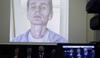 A photograph of the Russian cybercrime suspect Russian man Alexander Vinnik is on display on a screen during a press conference by his lawyers in Athens, Thursday, Feb. 28, 2019.   Zoe Konstantopoulou, the lawyer for Vinnik, suspected of bitcoin fraud and wanted by three countries says his health is deteriorating due to a hunger strike and criticized the Greek courts for holding him in custody for more than the maximum 18 months allowed. (AP Photo/Thanassis Stavrakis)