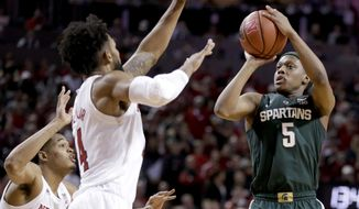 FILE - In this Jan. 17, 2019, file photo, Michigan State's Cassius Winston (5) shoots against Nebraska's James Palmer Jr. and Isaac Copeland Jr. (14) during the second half of an NCAA college basketball game in Lincoln, Neb. Winston has developed into a player of the year candidate, leading No. 6 Michigan State as it contends for a Big Ten title and perhaps top seeding in the NCAA tournament while two of its top players are injured. (AP Photo/Nati Harnik, File)