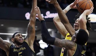 Minnesota guard Amir Coffey, top right, shoots against Northwestern center Dererk Pardon, left, and forward Vic Law during the first half of an NCAA college basketball game Thursday, Feb. 28, 2019, in Evanston, Ill. (AP Photo/Nam Y. Huh)