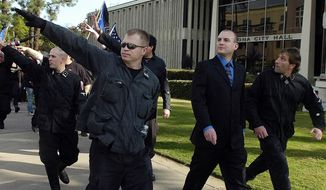 FILE-In this Saturday, Nov. 5, 2011 fule photo, Jeff Schoep, second right in business suit, commander of the National Socialist Movement, leave under police protection after a rally against illegal immigration in Pomona, Calif. One of the largest and oldest neo-Nazi groups in the U.S. appears to have an unlikely new leader: James Stern, a black activist who has vowed to dismantle it. Michigan corporate records indicate Stern replaced Jeff Schoep as the Detroit-based group's leader in January. Stern and Schoep didn't respond to requests for comment. (Thomas R. Cordova/The Orange County Register via AP)