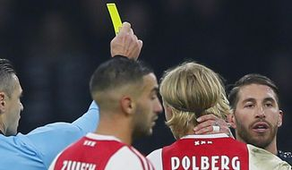 This Wednesday Feb. 13, 2019, image shows referee Damir Skomina, left, showing a yellow card to Real's Sergio Ramos, right, after a foul on Ajax's Kasper Dolberg during the first leg, round of sixteen, Champions League soccer match between Ajax and Real Madrid at the Johan Cruyff ArenA in Amsterdam, Netherlands. UEFA is investigating reported comments by Real Madrid captain Sergio Ramos that he intentionally got a yellow card to provoke a favorable Champions League ban. (AP Photo/Peter Dejong)