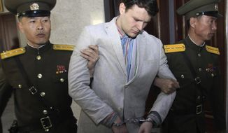 """FILE - In this March 16, 2016, file photo, American student Otto Warmbier, center, is escorted at the Supreme Court in Pyongyang, North Korea. President Donald Trump says he doesn't think North Korean leader Kim Jong Un was involved in the mistreatment of American college student Otto Warmbier, who died after being detained in the North. Trump says of Kim: """"He tells me that he didn't know about it, and I will take him at his word."""" The Ohio native was sentenced to 15 years of hard labor in North Korea on suspicion of stealing a propaganda poster. Warmbier died in 2017, shortly after being sent home in a coma.  (AP Photo/Jon Chol Jin, File)"""