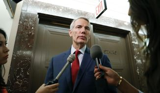 """FILE - In this Sept. 18, 2018 file photo, Sen. Rob Portman, R-Ohio, stops to answer questions for members of the media as he returns to a hearing on Capitol Hill in Washington. Portman said the United States shouldn't let North Korea """"off the hook"""" for its treatment of a college student who died soon after his release. The Republican senator has been in contact with Otto Warmbier's family since the suburban Cincinnati youth was imprisoned in early 2016 for allegedly stealing a propaganda banner. He died in June 2017 after returning in a vegetative state. His parents say he was tortured.  (AP Photo/Pablo Martinez Monsivais, File)"""