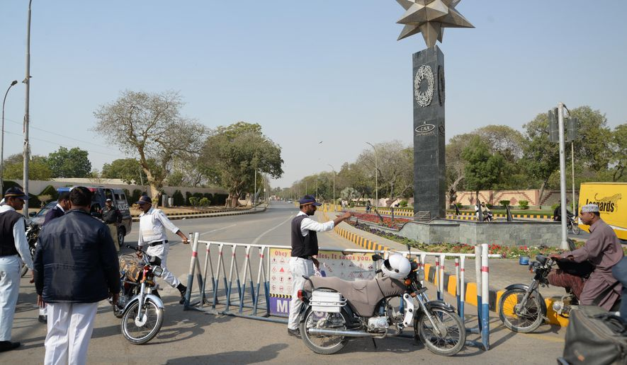 Pakistani police officers block a road to Karachi airport after it was close for civilian operations amid tension along the border with India, in Karachi, Pakistan, Wednesday, Feb. 27, 2019. Pakistan's military said Wednesday it shot down two Indian warplanes in the disputed region of Kashmir and captured a pilot, raising tensions between the nuclear-armed rivals. (AP Photo/Muhammad Rizwan)