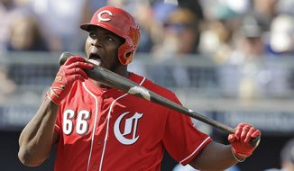 Cincinnati Reds' Yasiel Puig licks his bat during the third inning of a spring training baseball game against the Seattle Mariners, Monday, Feb. 25, 2019, in Peoria, Ariz. (AP Photo/Darron Cummings)