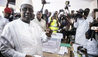 In this Sunday Feb. 24, 2019 file photo Senegal's incumbent President Macky Sall casts his vote during the presidential election at a polling station in Fatick, Senegal. Mr. Sall, along with Lutheran pastor Munib Younan, were awarded the Sunhak Peace Prize on Oct. 5, 2019, for their work promoting peace and prosperity in Africa and the Middle East. (AP Photo, File) **FILE**