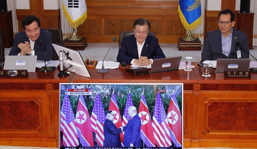 In this June 12, 2018, file photo, South Korean President Moon Jae-in, top center, watches the summit between U.S. President Donald Trump and North Korean leader Kim Jong-un in Singapore on a TV screen before the start of a weekly Cabinet meeting at the presidential Blue House in Seoul, South Korea. (Bee Jae-man/Yonhap via AP, File)