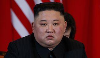 North Korean leader Kim Jong-un listens to President Donald Trump speak during a meeting, Thursday, Feb. 28, 2019, in Hanoi. (AP Photo/ Evan Vucci)