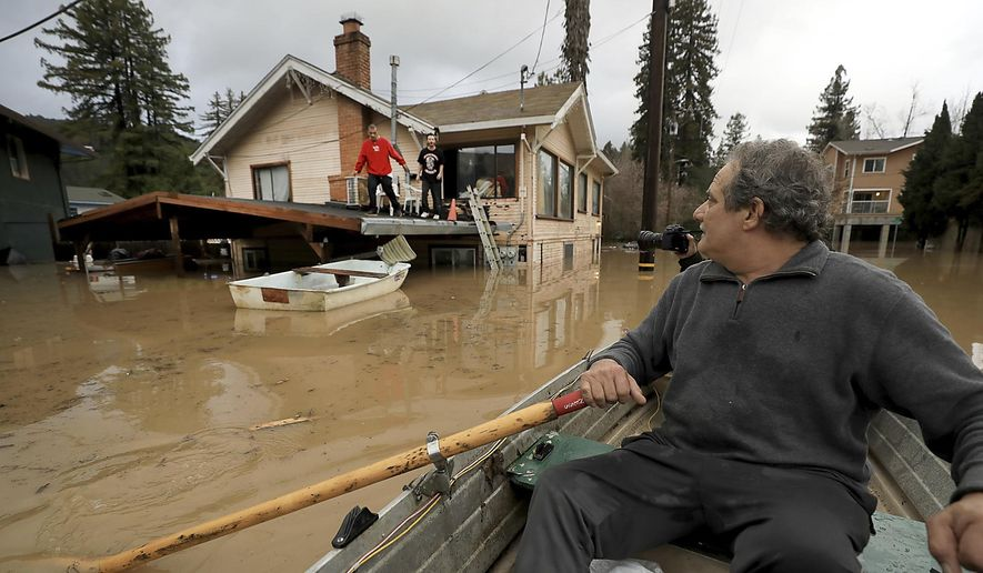 """Jonathan Von Renner checks on his son Jonathan Jr., and friend Emilio Ontivares in lower Guerneville, Calif., Wednesday, Feb. 27, 2019. Two Northern California communities are accessible only by boat after a rain-swollen river overflowed its banks following a relentless downpour. The Sonoma County Sheriff's Office says Guerneville, """"is officially an island"""" and another nearby town was also isolated by floodwaters. (Kent Porter/The Press Democrat via AP)"""