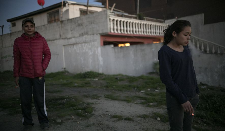 In this Feb. 8, 2019 photo, 17-year-old Honduran migrant Josue Mejia Lucero, left, smokes along with his girlfriend's sister Xiomara Henriquez Ayala, 13, outside the Agape World Mission shelter in Tijuana, Mexico. Xiomara and her sister Milagro are part of an untold number of Central American youths who traveled with a migrant caravan that crossed Mexico and landed in this crime-riddled city in November. (AP Photo/Emilio Espejel)