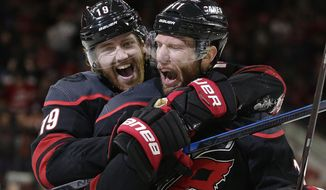 Carolina Hurricanes' Dougie Hamilton (19) celebrates with Jordan Staal (11) following Staal's goal against the St. Louis Blues' during the third period of an NHL hockey game in Raleigh, N.C., Friday, March 1, 2019. Carolina won 5-2. (AP Photo/Gerry Broome)