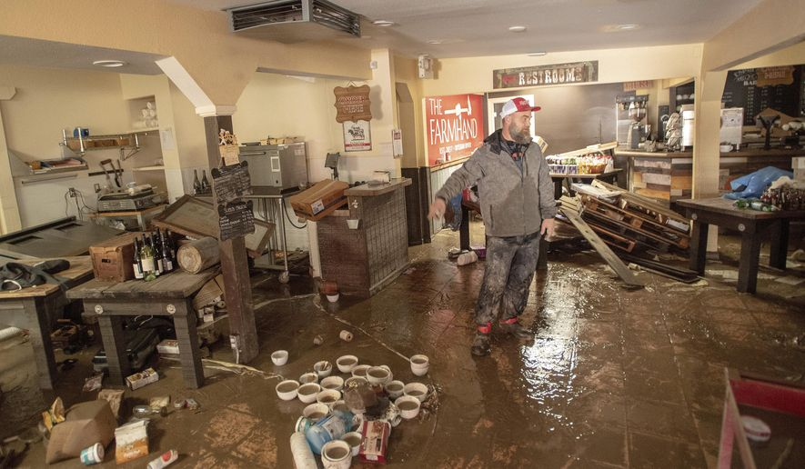 Farmhand Deli co-owner Jason Flint surveys the damage inside his restaurant along River Road as flood waters from the Russian River continue to recede in Guerneville, Calif., on Friday, March 1, 2019. Authorities have reopened the roads into two towns cut off for days by a rain-swollen river and residents and work crews have started cleaning up the muck that flooding left behind. (AP Photo/Josh Edelson)