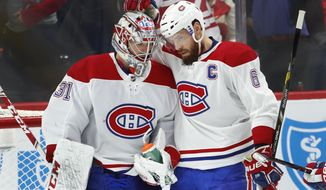 Montreal Canadiens goaltender Carey Price (31) celebrates with Shea Weber (6) after beating the Detroit Red Wings 8-1 after an NHL hockey game, Tuesday, Feb. 26, 2019, in Detroit. (AP Photo/Paul Sancya)