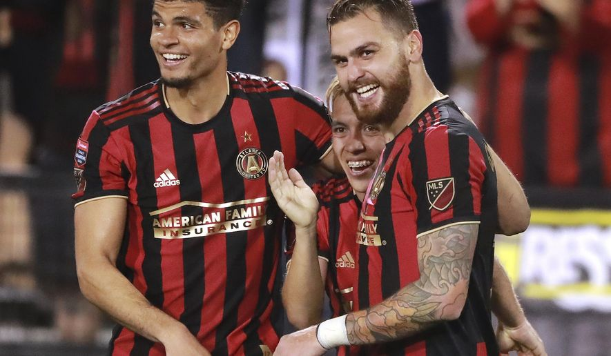 Atlanta United midfielder Leandro Gonzalez Pirez, right, celebrates his goal with Esequiel Barco, center, who had the assist, and Miles Robinson, against Herediano during a CONCACAF Champions League soccer match Thursday, Feb. 28, 2018, in Kennesaw, Ga. (Curtis Compton/Atlanta Journal Constitution via AP)