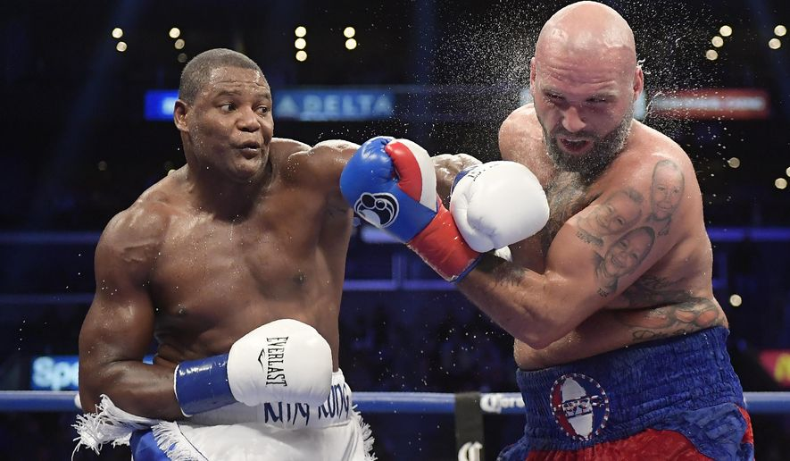 FILE - In this Dec. 1, 2018, file photo, Luis Ortiz, left, hits Travis Kauffman with a knockdown punch during the sixth round of a heavyweight boxing match in Los Angeles. Ortiz and fellow boxing star Erislandy Lara left behind their lives in Cuba for the ones they wanted for themselves and their families in the United States. (AP Photo/Mark J. Terrill, File)