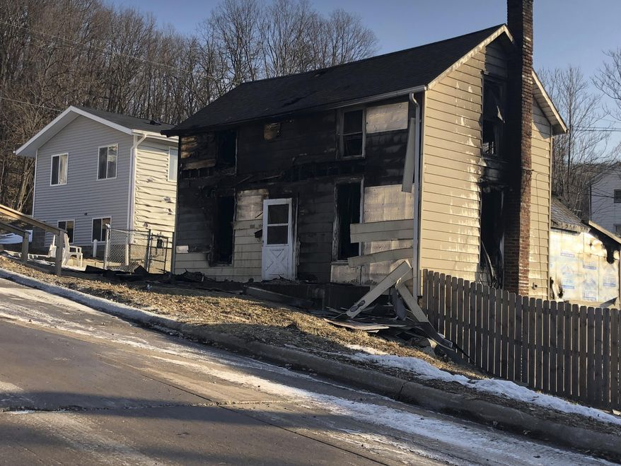 A heavily damaged a two-story house by a fire is seen Tuesday, Feb. 26, 2019, in Muscatine, Iowa.  Firefighters dispatched Monday found flames coming from several doors and windows, the Muscatine Fire Department said. Three bodies were found inside the home, one injured person found outside and was taken to Trinity Muscatine hospital in critical condition. (Jim Meenan/Muscatine Journal via AP)