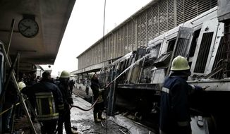 Firefighters hose down a train that was damaged after a crash inside Ramsis train station in Cairo, Egypt, Wednesday, Feb. 27, 2019. An Egyptian medical official said at least 20 people have been killed and dozens injured after a railcar rammed into a barrier inside the station causing an explosion of the fuel tank and triggering a huge blaze that engulfed that part of the station. The head of the Cairo Railroad Hospital said the death toll is expected to rise further. (AP Photo/Nariman El-Mofty) ** FILE **