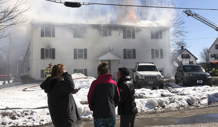 Residents watch as firefighters battling a four-alarm fire at a three-story apartment building, Friday, March 1, 2019, in Berwick, Maine. Authorities say at least five firefighters were hurt containing the blaze. (Deb Cram/Foster's Daily Democrat via AP)