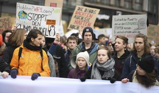 Swedish climate activist Greta Thunberg, front with white cap, attends a protest rally in Hamburg, Germany, Friday, March 1, 2019. (Daniel Reinhardt/dpa via AP)