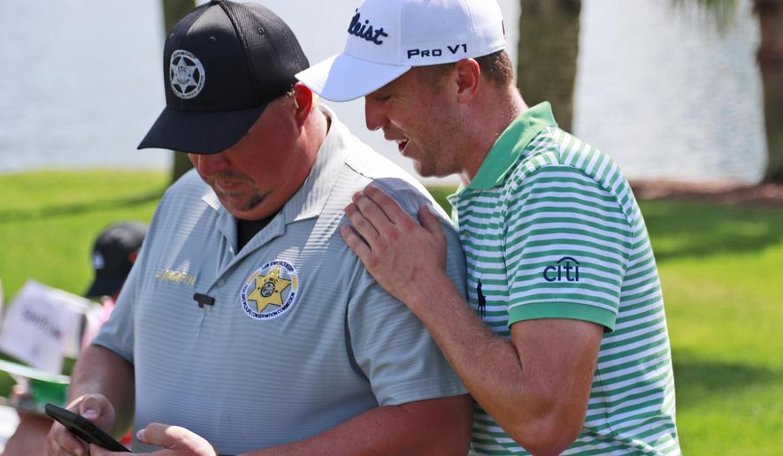 Justin Thomas, right, looks at the phone of Florida Fish and Wildlife Conservation Commission officer John Booth on the third hole during the second round of the Honda Classic golf tournament, Friday, March 1, 2019, in Palm Beach Gardens, Fla. (AP Photo/Wilfredo Lee)