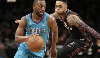 Charlotte Hornets' Kemba Walker, left, drives past Brooklyn Nets' D'Angelo Russell during the first half of an NBA basketball game Friday, March 1, 2019, in New York. (AP Photo/Seth Wenig)