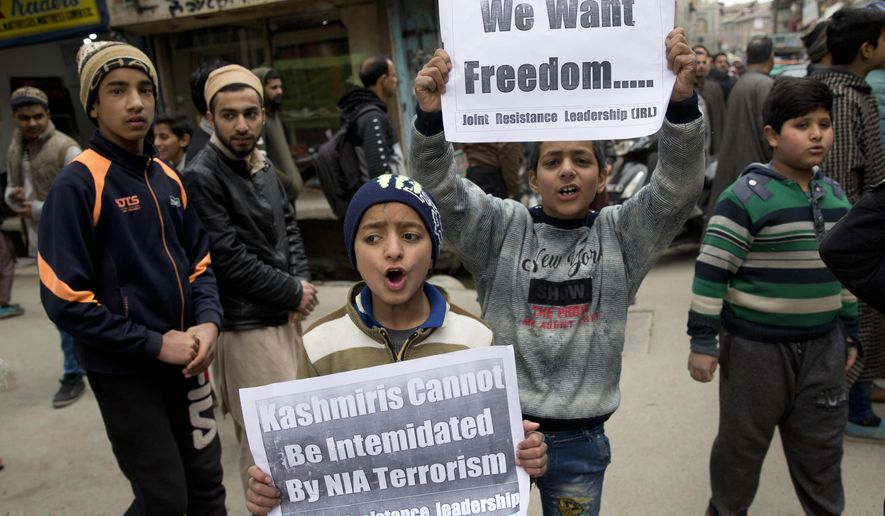 Kashmiri children hold placards and shout freedom slogans in Srinagar, Indian controlled Kashmir, Friday, March 1, 2019. India has banned Jama'at-e-Islami, a political-religious group in Kashmir, in a sweeping and ongoing crackdown against activists seeking the end of Indian rule in the disputed region amid the most serious confrontation between India and Pakistan in two decades. (AP Photo/ Dar Yasin)