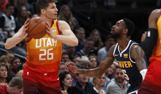 Utah Jazz guard Kyle Korver, left, looks to pass the ball as Denver Nuggets guard Will Barton defends during the first half of an NBA basketball game Thursday, Feb. 28, 2019, in Denver. (AP Photo/David Zalubowski)