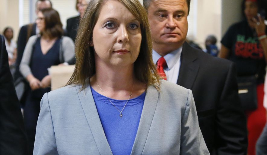 FILE - In this Wednesday, May 17, 2017 file photo, Betty Shelby leaves the courtroom with her husband, Dave Shelby, right, after the jury in her case began deliberations in Tulsa, Okla. The Department of Justice says there is insufficient evidence to pursue federal civil rights charges against the white former Tulsa police officer who shot and killed an unarmed black man. U.S. Attorney Trent Shores on Friday, March 1, 2019, announced the closure of the federal investigation into whether ex-Tulsa police officer Betty Shelby willfully used unreasonable force against Terence Crutcher when she shot and killed him in September 2016. (AP Photo/Sue Ogrocki, File)