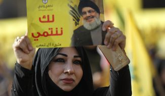 "FILE - In this April 13, 2018, file photo, a supporter of Hezbollah leader Sayyed Hassan Nasrallah holds up his portrait with Arabic words that read: ""We belong with you,"" during an election campaign speech in a southern suburb of Beirut, Lebanon. The Lebanese Hezbollah group has strongly rejected the British government's move to ban the group as a ""terrorist organization."" (AP Photo/Hussein Malla, File)"