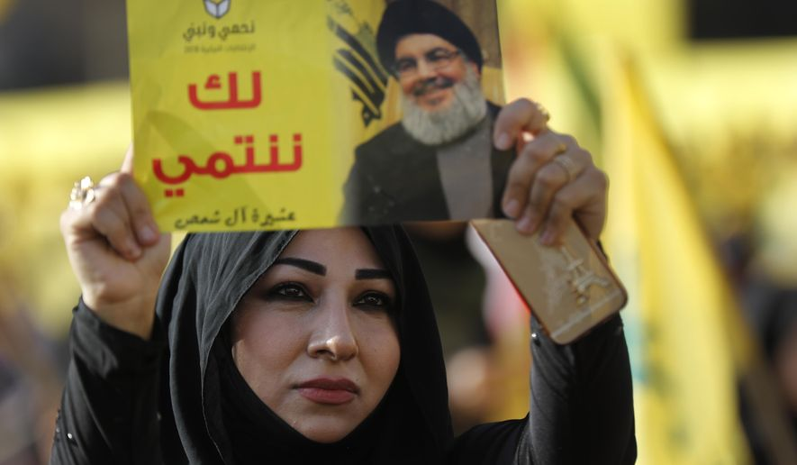 """FILE - In this April 13, 2018, file photo, a supporter of Hezbollah leader Sayyed Hassan Nasrallah holds up his portrait with Arabic words that read: """"We belong with you,"""" during an election campaign speech in a southern suburb of Beirut, Lebanon. The Lebanese Hezbollah group has strongly rejected the British government's move to ban the group as a """"terrorist organization."""" (AP Photo/Hussein Malla, File)"""