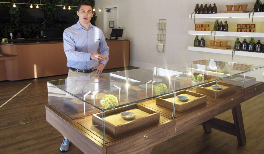 Pat Doherty, director of new market development for Acreage Holdings, describes products inside a display case at The Botanist in Fargo, N.D., Thursday, Feb. 28, 2019. The business located in a south-side mini-mall is North Dakota's first medical marijuana dispensary. North Dakota voters approved the drug in November 2016, after lawmakers refused to do it. (AP Photo/Dave Kolpack)