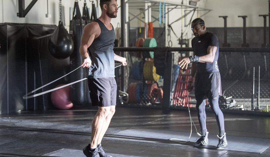 """In this undated image provided courtesy of Centr, actor Chris Hemsworth, left, and Michael Olajide Jr. workout. When Hemsworth sought """"experts"""" to contribute to a fitness and health app called Centr, one place he turned was to the boxing ring. He found Olajide Jr., a former middleweight contender who literally lost an eye to his sport. (Courtesy of Centr via AP)"""