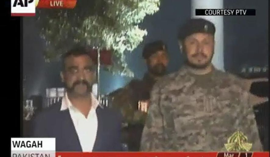 """In this image made from video provided by PTV,  Wing Commander Abhinandan Varthaman walks to cross the border into India, in Wagah, Pakistan, Friday, March 1, 2019. Pakistani officials have handed an Indian pilot captured from a downed plane over to India at the border crossing at Wagah in a """"gesture of peace"""" promised by Prime Minister Imran Khan amid a dramatic escalation with India this week over the disputed region of Kashmir. The pilot was expected to travel to New Delhi for a debriefing with top Indian officials about the time he spent captive. (PTV via AP)"""