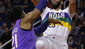 New Orleans Pelicans forward Anthony Davis (23) shoots over Phoenix Suns forward Richaun Holmes in the first half during an NBA basketball game, Friday, March 1, 2019, in Phoenix. (AP Photo/Rick Scuteri)