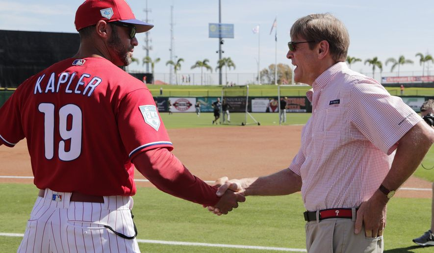 Philadelphia Phillies manager Gabe Kapler (19) shakes hands with team owner John Middleton before a spring training baseball game against the Pittsburgh Pirates, Friday, March 1, 2019, in Clearwater, Fla. (AP Photo/Lynne Sladky)