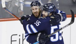 Winnipeg Jets' Kevin Hayes (12) and Mark Scheifele (55) celebrate Hayes' his first goal for the Jets since his recent trade to the team, against the Nashville Predators during the third period of an NHL hockey game Friday, March 1, 2019, in Winnipeg, Manitoba. (John Woods/The Canadian Press via AP)