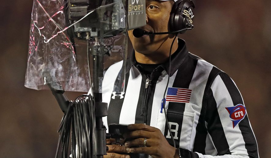 FILE - In this Nov. 3, 2018, file photo, referee Reggie Smith reviews a targeting penalty during the first half of an NCAA college football game between Oklahoma and Texas Tech, in Lubbock, Texas. The NCAA football rules committee has proposed giving replay officials more leeway to overturn targeting fouls. The rules committee met in Indianapolis this week and announced on Friday, March 1, 2019, its proposed changes. The proposals must be approved by the football oversight committee in April. They would go into effect next season. (AP Photo/Brad Tollefson, File)