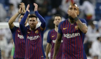 Barcelona forward Lionel Messi, left, applauds fans at the end of the Copa del Rey semifinal second leg soccer match between Real Madrid and FC Barcelona at the Bernabeu stadium in Madrid, Spain, Wednesday Feb. 27, 2019. (AP Photo/Andrea Comas)