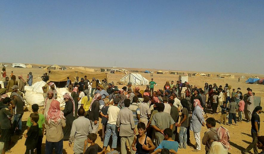 FILE - In this Aug. 4, 2016, file, photo, people gather to take basic food stuffs and other aid from community leaders charged with distributing equitably the supplies to the 64,000-person refugee camp called Rukban on the Jordan-Syria border. The Russian military says the Syrian government is sending convoys to evacuate a refugee camp in southern Syria where tens of thousands suffer from lack of food and medical supplies. Col. Gen. Mikhail Mizintsev said the Syrian convoys are heading on Friday, March 1, 2019 to the Rukban camp and urged the U.S. military in the area to secure its safe passage.  (AP Photo, File)
