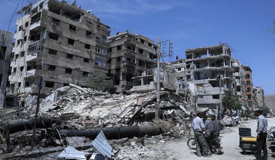 In this Monday, April 16, 2018, file photo, people stand in front of damaged buildings, in the town of Douma, the site of a suspected chemical weapons attack, near Damascus, Syria. (AP Photo/Hassan Ammar) ** FILE **