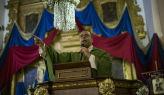 In this Feb. 9, 2019 photo, Monsignor Hector Lunar delivers his homily during a Mass in the Dulce Nombre de Jesus church, in the Petare slum of Caracas, Venezuela. Monsignor Hector Lunar, a beloved priest in one of Latin America's largest slums, has fallen under attack by loyalists of President Nicolas Maduro for using the pulpit to hold the embattled socialist leader responsible for suffering among his poor parishioners. (AP Photo/Rodrigo Abd)