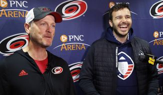 FILE - In this Feb. 19, 2019, file photo, Tom Dundon, left, majority owner of the Carolina Hurricanes, and Charlie Ebersol, co-founder and CEO of the Alliance of American Football, talk to the media about Dundon's $250 million investment in the league, before an NHL hockey game between the New York Rangers and the Hurricanes in Raleigh, N.C. Its too early to tell what impact the Alliance of American Football will have on the sport itself. After all, this is its fourth weekend of games. Away from the field, with an infusion of backing from Dundon, the AAF is finding its footing. Its also finding what Ebersol calls substantial interest in the league in such areas as sponsorships and partnerships, with three new partners signing on since the season opener three weeks ago. (AP Photo/Chris Seward, File) **FILE**