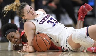 Connecticut's Katie Lou Samuelson, top and Houston's Julia Blackshell-Fair fall to the court chasing a loose ball during the first half of an NCAA college basketball game, Saturday, March 2, 2019, in Storrs, Conn. Samuelson left the game injured after the play. (AP Photo/Jessica Hill)