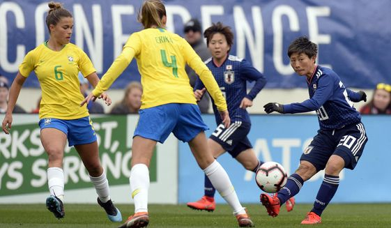 Japan forward Kumi Yokoyama (20) passes the ball past Brazil defenders Tamires (6) Erika (4) during the first half of a SheBelieves Cup women's soccer match Saturday, March 2, 2019, in Nashville, Tenn. (AP Photo/Mark Zaleski)