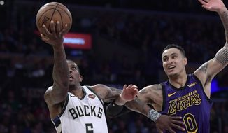 Milwaukee Bucks guard Eric Bledsoe, left, shoots as Los Angeles Lakers forward Kyle Kuzma defends during the second half of an NBA basketball game Friday, March 1, 2019, in Los Angeles. The Bucks won 131-120. (AP Photo/Mark J. Terrill)