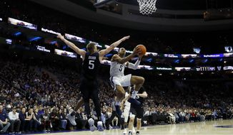 Villanova's Phil Booth, center, goes up for shot against Butler's Paul Jorgensen during the first half of an NCAA college basketball game, Saturday, March 2, 2019, in Philadelphia. (AP Photo/Matt Slocum)