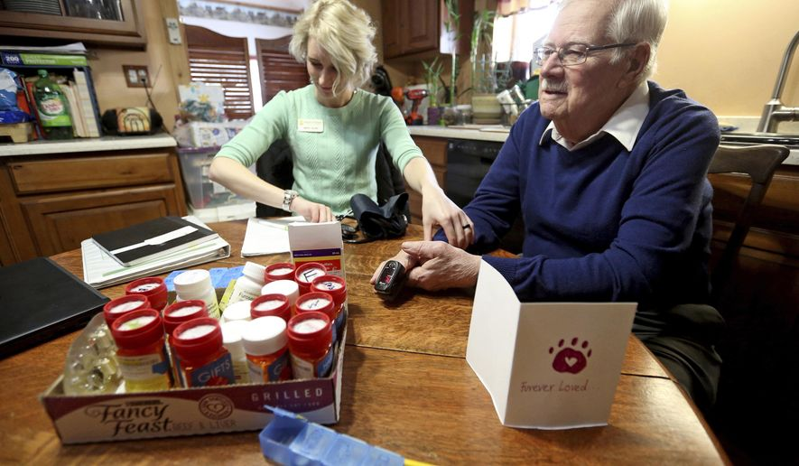 """In this Jan. 25, 2019, photo, Kristin Schroeder, a Hospice of Dubuque nurse, takes vitals on Paul """"Jack"""" Papin during a visit at his home in Dubuque, Iowa. (Jessica Reilly/Telegraph Herald via AP)"""